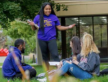 Diversity photo of students engaged in conversation on the campus lawn.