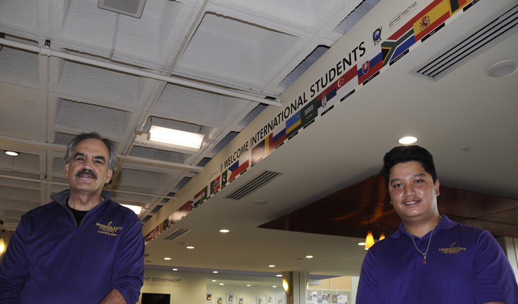 Sanjaya Balami and CSU Director Mark Constantine in front of the new international flag display in the student union.